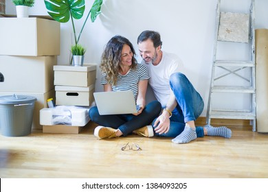 Middle age senior romantic couple in love sitting on the apartment floor with boxes around and using computer laptop smiling happy for moving to a new home