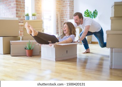 Middle age senior romantic couple having fun riding inside of cardboard, excited and smiling happy for moving to a new home