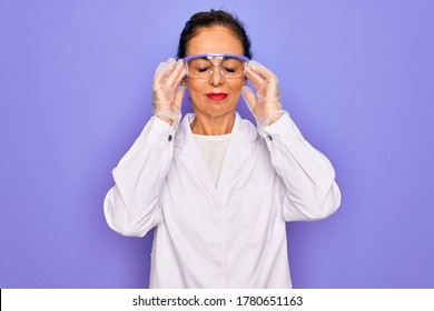 Middle age senior scientist woman wearing coat and laboratory glasses over purple background suffering from headache desperate and stressed because pain and migraine. Hands on head.