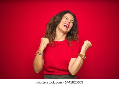 Middle age senior woman with curly hair over red isolated background very happy and excited doing winner gesture with arms raised, smiling and screaming for success. Celebration concept.