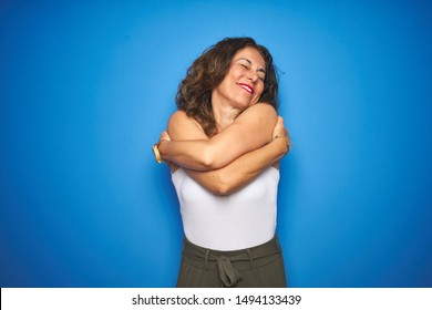 Middle age senior woman with curly hair standing over blue isolated background Hugging oneself happy and positive, smiling confident. Self love and self care