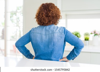 Middle age senior woman with curly hair wearing denim jacket at home standing backwards looking away with arms on body