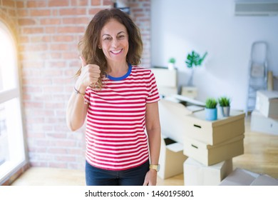 Middle age senior woman moving to a new house packing cardboard boxes doing happy thumbs up gesture with hand. Approving expression looking at the camera with showing success.