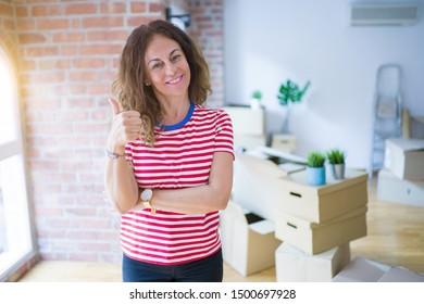 Middle age senior woman moving to a new house packing cardboard boxes smiling with happy face looking and pointing to the side with thumb up.