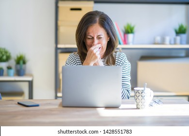 Middle age senior woman sitting at the table at home working using computer laptop smelling something stinky and disgusting, intolerable smell, holding breath with fingers on nose. Bad smells concept.