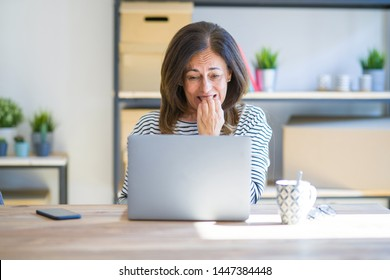Middle age senior woman sitting at the table at home working using computer laptop looking stressed and nervous with hands on mouth biting nails. Anxiety problem.