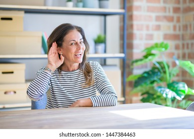 Middle age senior woman sitting at the table at home smiling with hand over ear listening an hearing to rumor or gossip. Deafness concept.