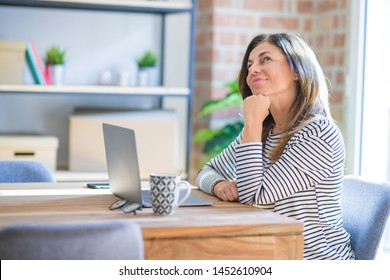 Middle age senior woman sitting at the table at home working using computer laptop serious face thinking about question, very confused idea