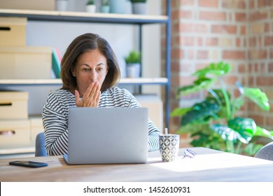 Middle age senior woman sitting at the table at home working using computer laptop cover mouth with hand shocked with shame for mistake, expression of fear, scared in silence, secret concept