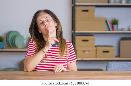 Middle age senior woman sitting at the table at home Thinking concentrated about doubt with finger on chin and looking up wondering