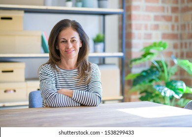 Middle age senior woman sitting at the table at home happy face smiling with crossed arms looking at the camera. Positive person.