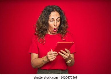Middle age senior woman using touchpad tablet over red isolated background scared in shock with a surprise face, afraid and excited with fear expression