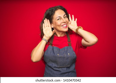 Middle age senior woman wearing apron uniform over red isolated background Trying to hear both hands on ear gesture, curious for gossip. Hearing problem, deaf