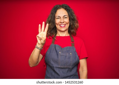 Middle age senior woman wearing apron uniform over red isolated background showing and pointing up with fingers number three while smiling confident and happy.