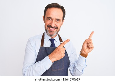 Middle age shopkeeper man wearing apron standing over isolated white background smiling and looking at the camera pointing with two hands and fingers to the side.