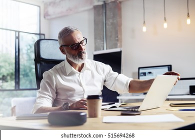 Middle age top manager wearing a classic glasses and working at the wood table in modern interior design office.Stylish bearded businessman using laptop on workplace. Horizontal,blurred