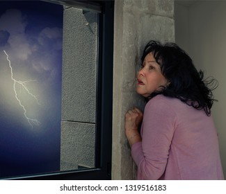 A middle age woman is afraid of thunderstorm stands in the corner of the room and watches the lighting through the window.