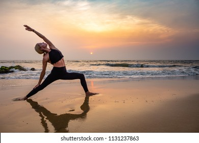 Middle age woman in black doing yoga on sand beach in India  standing asana virabhadrasana at sunset. Healthy lifestyle.