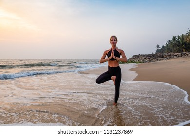 Middle age woman in black doing yoga on sand beach in India at sunset. Vrikshasana (tree pose). Healthy lifestyle.