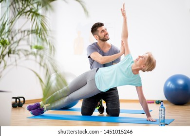 Middle age woman exercising on blue mat during physiotherapy with young male doctor