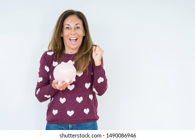 Middle age woman holding piggy bank over isolated background screaming proud and celebrating victory and success very excited, cheering emotion