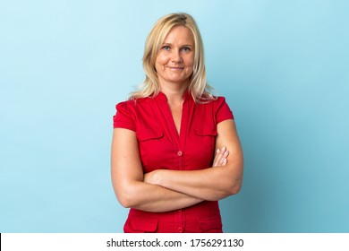 Middle age woman isolated on blue background keeping the arms crossed in frontal position