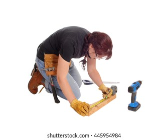 A middle age woman kneeling on the floor and working with some toolsmeasuring, isolated for white background.