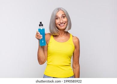 Eine Frau im mittleren Alter, die glücklich und angenehm überrascht aussieht, begeistert von einem faszinierten und schockierten Ausdruck. Fitnesskonzept