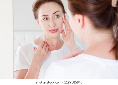 Middle age woman looking in mirror on face. Wrinkles and anti aging skin care concept. Selective focus