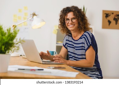 Middle age woman at the office working with a  laptop