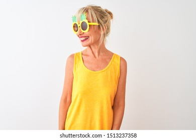 Middle age woman on vacation wearing pineapple sunglasses over isolated white background looking away to side with smile on face, natural expression. Laughing confident.