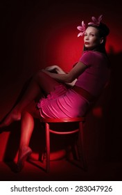 Middle age woman in pink evening dress under artistic light