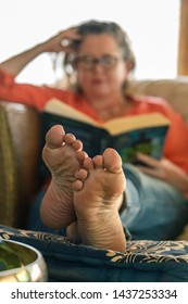 middle age woman reading and relaxing on the couch with the legs up.