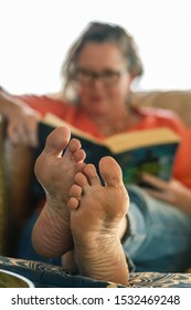 middle age woman reading and relaxing on the couch