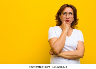 middle age woman thinking, feeling doubtful and confused, with different options, wondering which decision to make against yellow wall