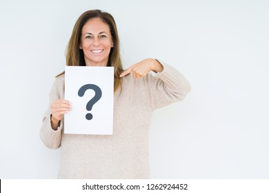 Middle age woman thinking and holding paper with question mark symbol over isolated background with surprise face pointing finger to himself