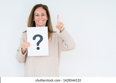 Middle age woman thinking and holding paper with question mark symbol over isolated background surprised with an idea or question pointing finger with happy face, number one