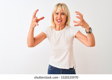 Middle age woman wearing casual t-shirt standing over isolated white background Shouting frustrated with rage, hands trying to strangle, yelling mad
