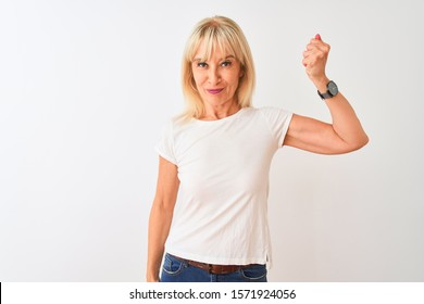 Middle age woman wearing casual t-shirt standing over isolated white background Strong person showing arm muscle, confident and proud of power