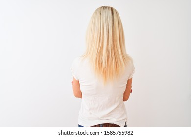 Middle age woman wearing casual t-shirt standing over isolated white background standing backwards looking away with crossed arms