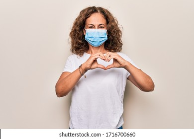 Middle age woman wearing coronavirus protection mask for covid-19 epidemic virus smiling in love doing heart symbol shape with hands. Romantic concept.