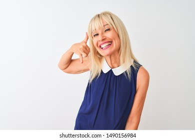 Middle age woman wearing elegant blue dress standing over isolated white background smiling doing phone gesture with hand and fingers like talking on the telephone. Communicating concepts.