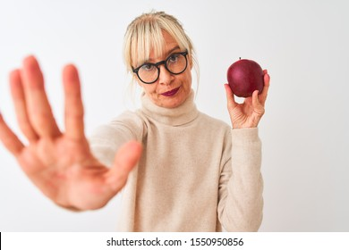 Middle age woman wearing glasses holding apple standing over isolated white background with open hand doing stop sign with serious and confident expression, defense gesture