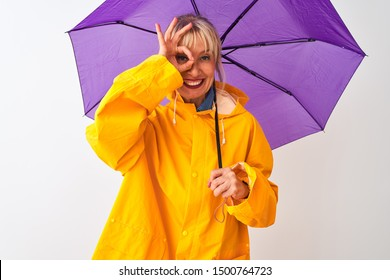 Middle age woman wearing rain coat and purple umbrella over isolated white background with happy face smiling doing ok sign with hand on eye looking through fingers