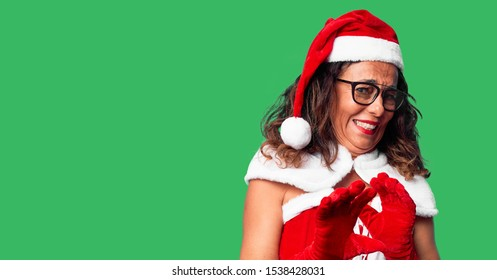 Middle age woman wearing Santa Claus costume disgusted expression, displeased and fearful doing disgust face because aversion reaction. With hands raised. Annoying concept.