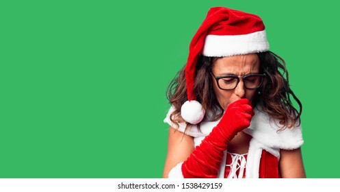 Middle age woman wearing Santa Claus costume feeling unwell and coughing as symptom for cold or bronchitis. Healthcare concept.