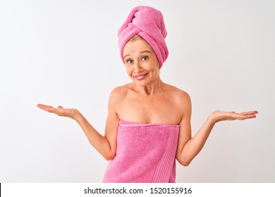 Middle age woman wearing shower towel after bath standing over isolated white background clueless and confused expression with arms and hands raised. Doubt concept.