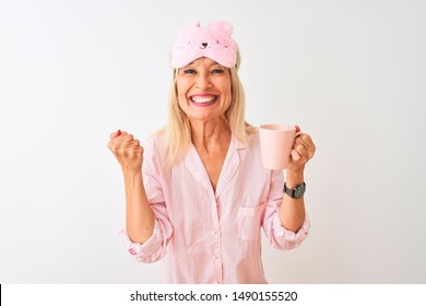 Middle age woman wearing sleep mask pajama drinking coffee over isolated white background screaming proud and celebrating victory and success very excited, cheering emotion
