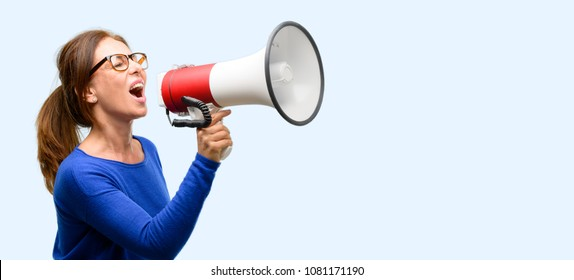 Middle age woman wearing wool sweater and glasses communicates shouting loud holding a megaphone, expressing success and positive concept, idea for marketing or sales isolated blue background