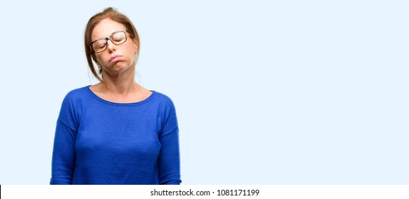 Middle age woman wearing wool sweater and glasses with sleepy expression, being overworked and tired isolated blue background